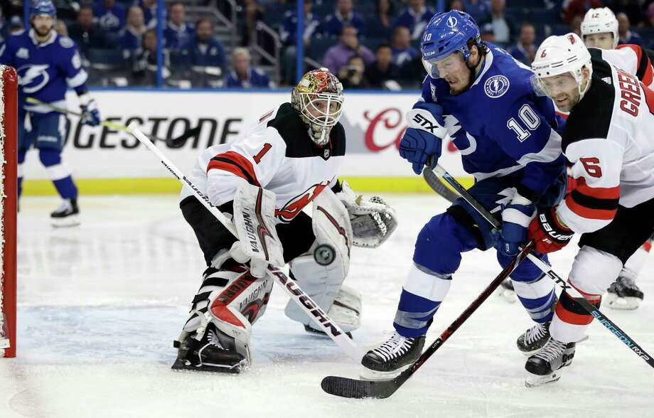 Tampa Bay Lightning center J.T. Miller (10) and New Jersey Devils defenseman Andy Greene (6) chase a rebound off Devils goaltender Keith Kinkaid during the second period of Game 1 of an NHL first-round hockey playoff series Thursday, April 12, 2018, in Tampa, Fla. (AP Photo/Chris O'Meara) Photo: Chris O'Meara / Copyright 2018 The Associated Press. All rights reserved.