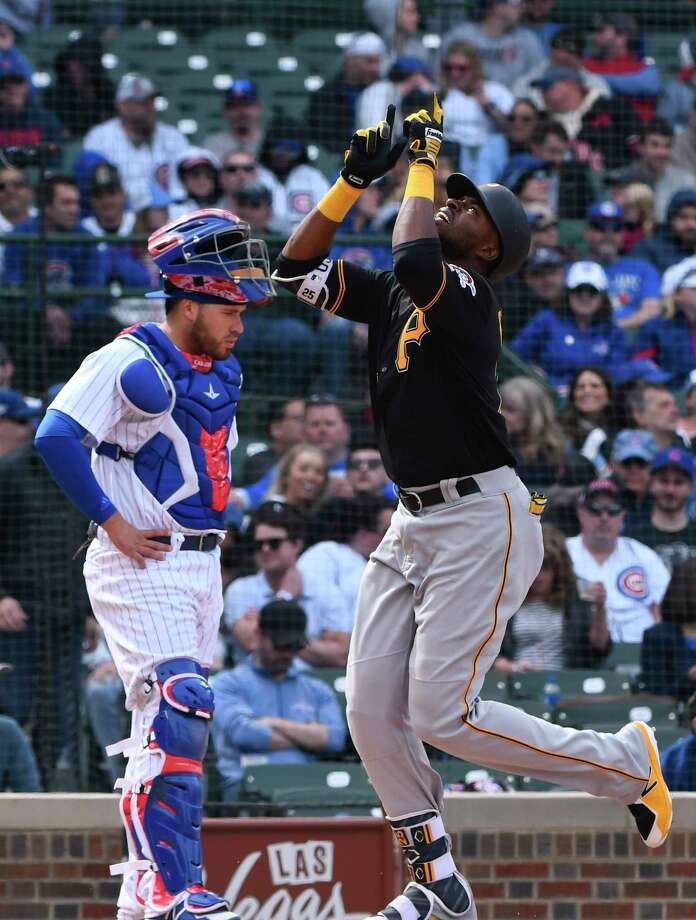 Pittsburgh Pirates' Gregory Polanco, right, points to the sky as he crosses home plate in front of Chicago Cubs catcher Victor Caratini (7) after hitting a home run in the seventh inning of a baseball game, Thursday, April 12, 2018, in Chicago. (AP Photo/Matt Marton) Photo: Matt Marton / FR170980 AP