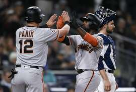 San Francisco Giants' Andrew McCutchen, center, celebrates with Joe Panik, left, after both scored on a double by Buster Posey during the sixth inning of a baseball game as San Diego Padres catcher Austin Hedges looks on in San Diego, Thursday, April 12, 2018. (AP Photo/Kelvin Kuo)