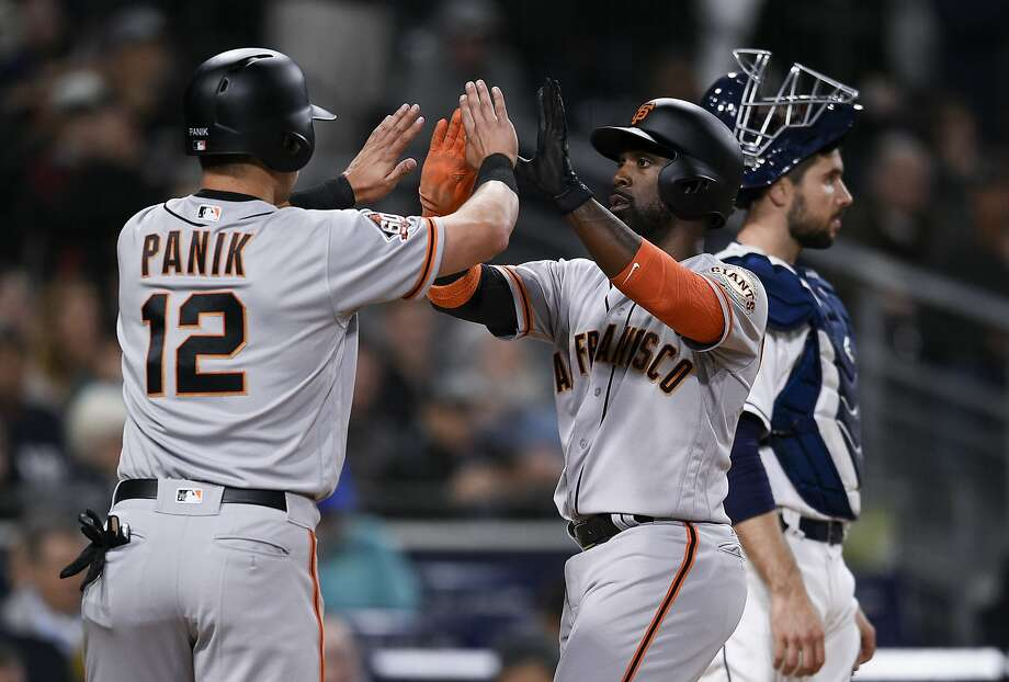 San Francisco Giants' Andrew McCutchen, center, celebrates with Joe Panik, left, after both scored on a double by Buster Posey during the sixth inning of a baseball game as San Diego Padres catcher Austin Hedges looks on in San Diego, Thursday, April 12, 2018.  Photo: Kelvin Kuo / Associated Press
