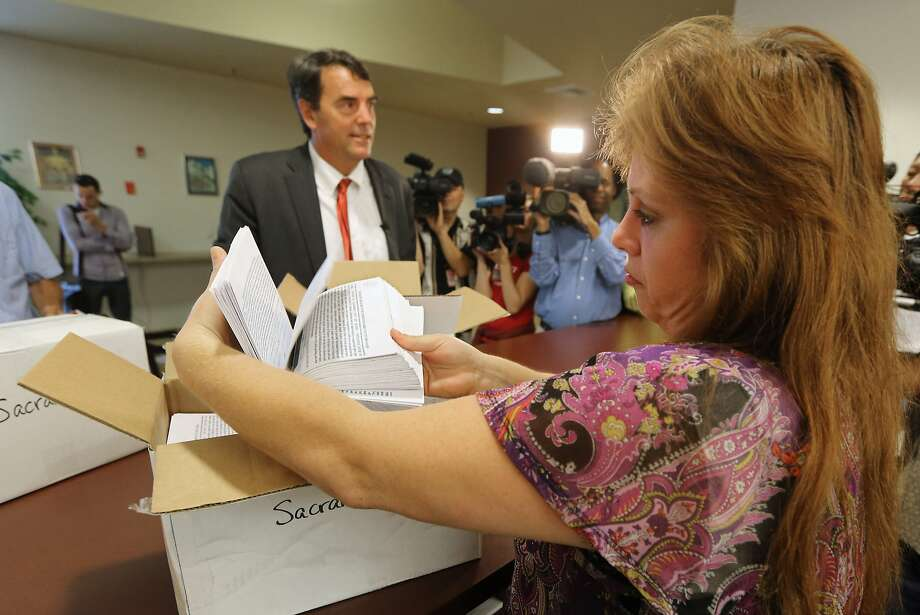 Heather Ditty, elections manager for the Sacramento County Registrar of Voters, makes a quick inspection of some of the petitions turned in by Silicon Valley venture capitalist Tim Draper, left, that would place a ballot initiative before voters asking to split California into six separate states, Tuesday, July 15, 2014, in Sacramento, Calif.  Draper delivered what he said were 44,000 signatures, of the 1.3 million the Six California's campaign plans to submit statewide this week.  If enough signatures are verified,  voters in November 2016 would be asked to divide the state into six states called Jefferson, North California, Silicon Valley, Central California, West California and South California. (AP Photo/Rich Pedroncelli) Photo: Rich Pedroncelli / Associated Press