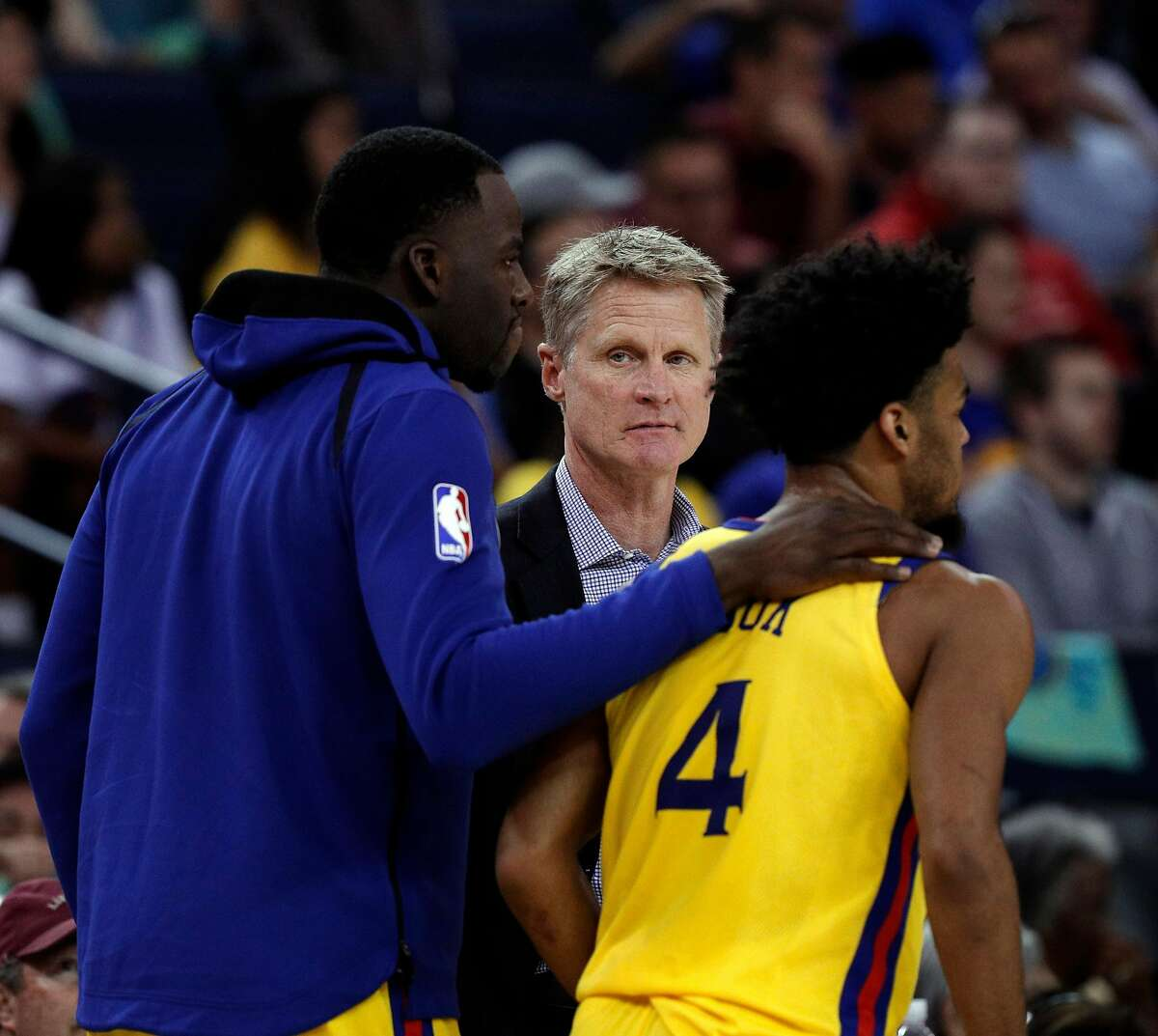 Warriors head coach Steve Kerr watches as Draymond Green helps Quinn Cook with some advice during the Golden State Warriors game against the Milwaukee Bucks at Oracle Arena in Oakland, Calif., on Thursday, March 29, 2018.