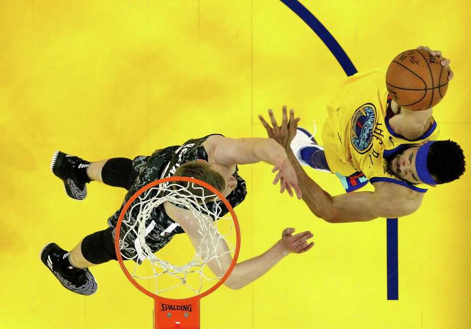 JaVale McGee (1) goes up for a slam over Davis Bertans (42) in the second half as the Golden State Warriors played the San Antonio Spurs at Oracle Arena in Oakland, Calif., on Thursday, March 8, 2018. Photo: Carlos Avila Gonzalez, Staff Photographer / The Chronicle / San Francisco Chronicle - Carlos Avila Gonzalez