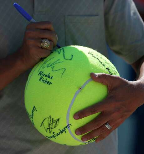 Giant tennis balls are a huge hit with kids who collect players' autographs throughout the week. This collector astutely notes the players' names below their signatures. Photo: Karen Warren / © 2018 Houston Chronicle