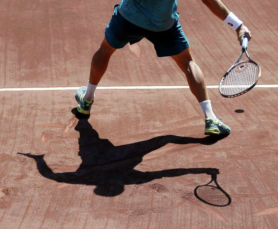 Nicolas Kicker casts a shadow on the clay as he competes against Donald Young. Photo: Karen Warren / © 2018 Houston Chronicle