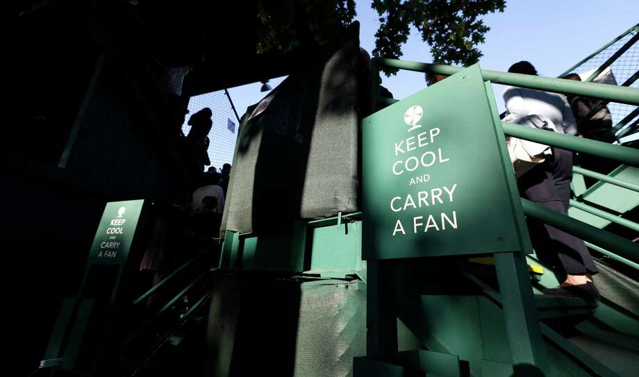 To beat the heat, signs near the entrance to center court encourage spectators to pick up handheld fans during Tuesday's competition. Photo: Karen Warren / © 2018 Houston Chronicle