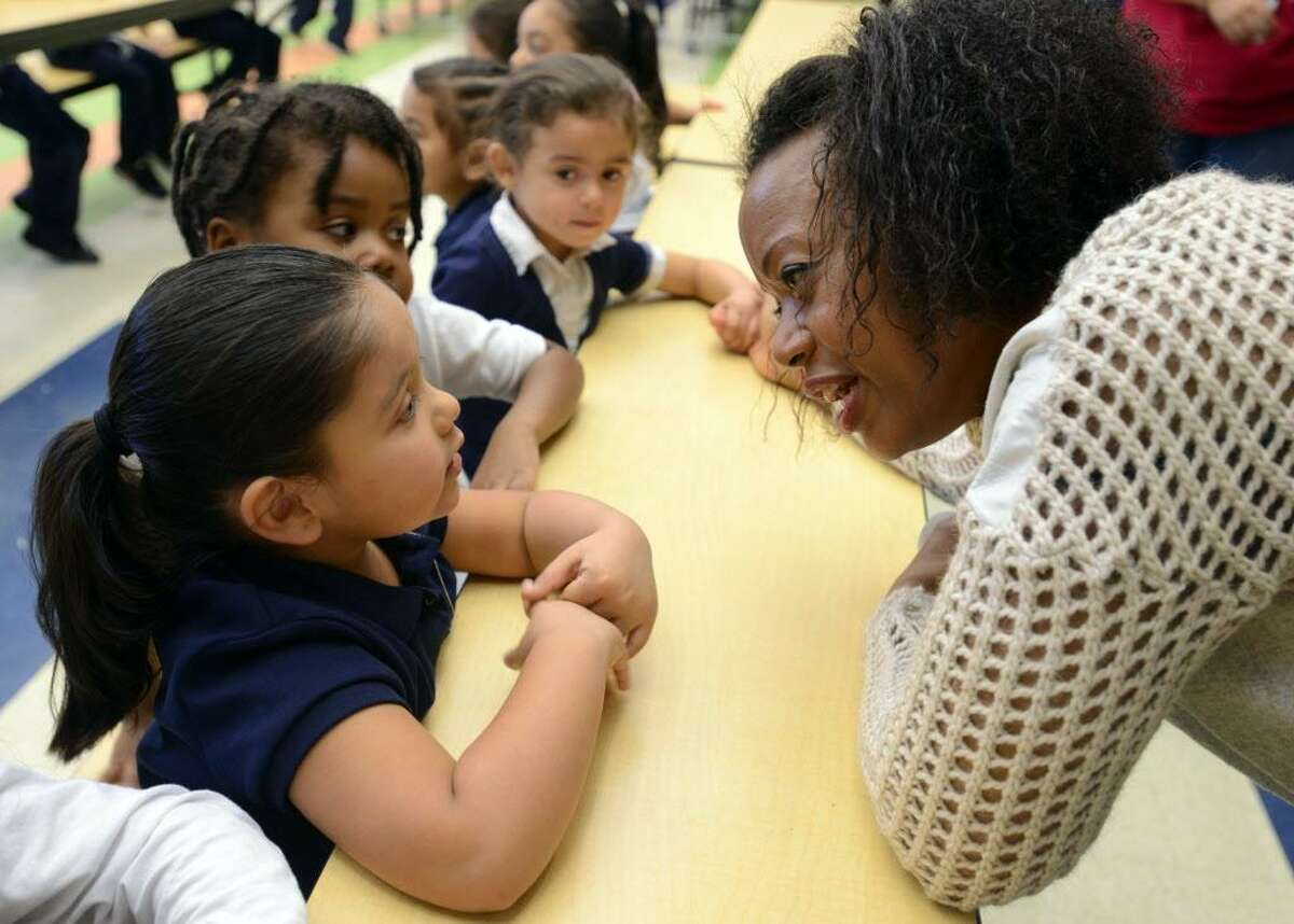 Designer Tracy Reese talks fashion with pre-k student Cassandra Santoyo Friday, Nov. 20, 2015, at Barnum School in Bridgeport, Conn. Reese was viting her adopted Turnaround Arts school to brainstorm with kids on a design project to enhance their school uniform.