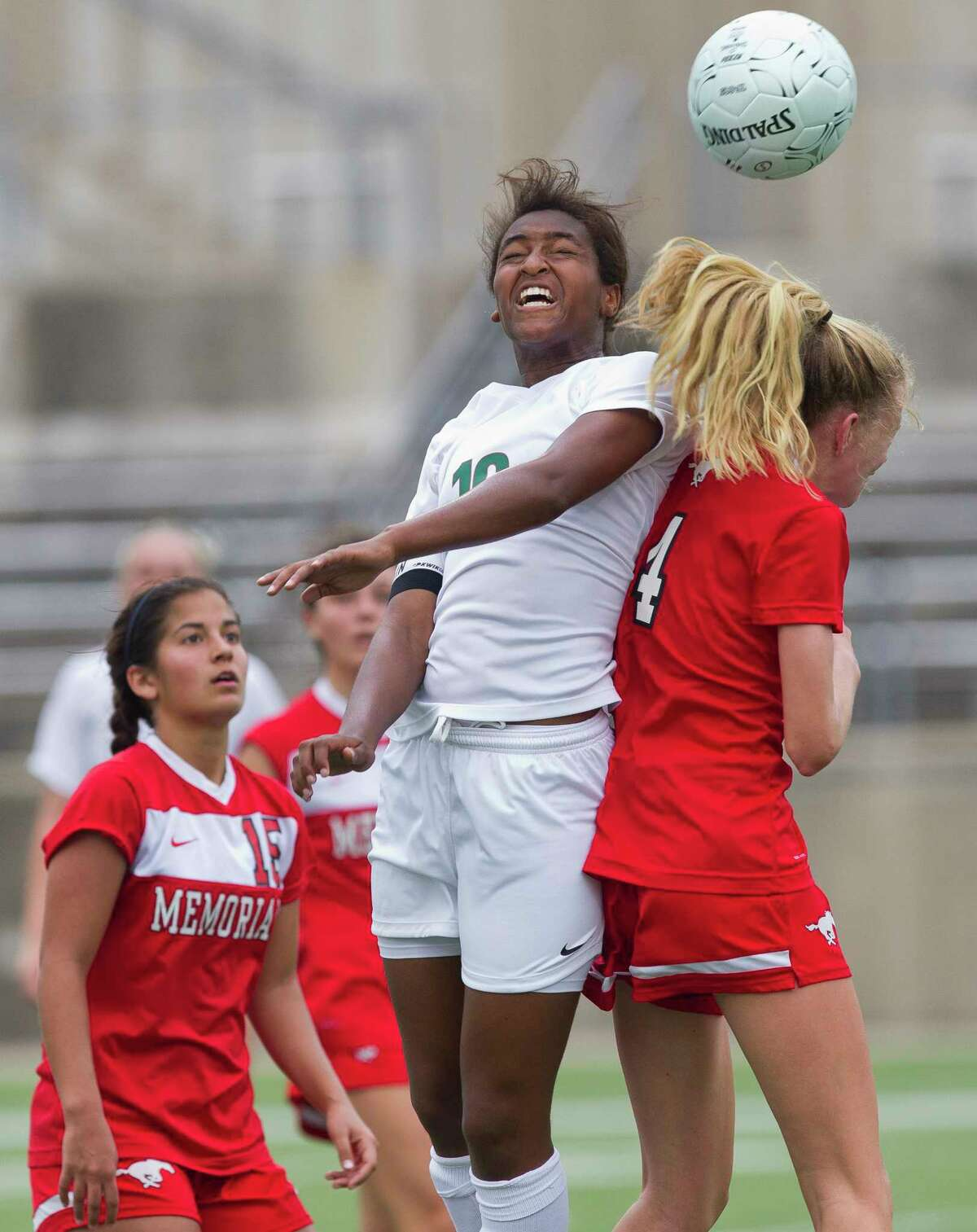 The Woodlands forward Jazzy Richards (16) goes for a header against Memorial midfielder Blakeley Buckingham (4) during the first period of a Region II-6A regional semifinal match at the Kelly Reeves Athletic Complex, Friday, April 13, 2018, in Round Rock.