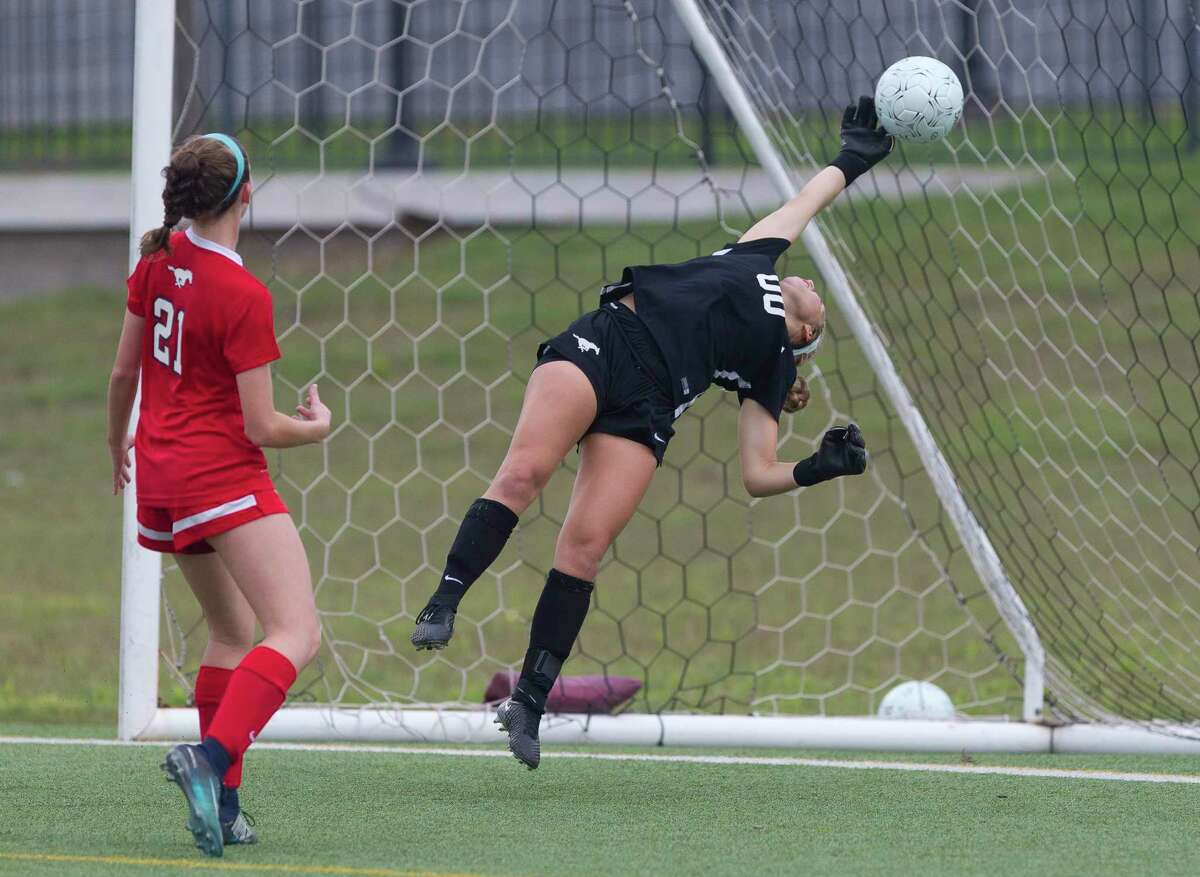 Memorial goalie Bella Killgore (00) makes a stop during the first period of a Region II-6A regional semifinal match at the Kelly Reeves Athletic Complex, Friday, April 13, 2018, in Round Rock.