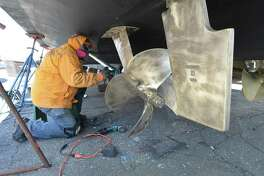 Norm Allen from Fairfield uses a wire polishing wheel to clean the drive shaft, propeller and rudder of barnacles and rust on his 52ft pleasure boat at Cove Marina on Sunday April 8, 2018 in Norwalk.