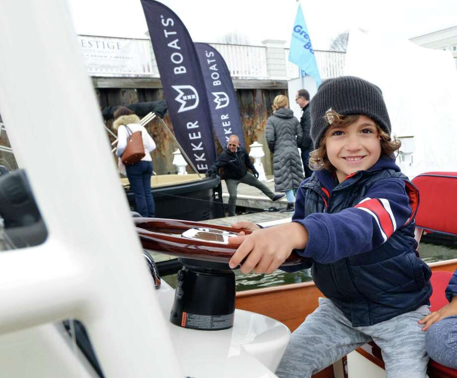 Mason Holl, 7, of Westport, smiled as he took the wheel of a motorboat during the 10th annual Greenwich Boat Show at the Greenwich Water Club April 7. Photo: Bob Luckey Jr. / Hearst Connecticut Media / Greenwich Time