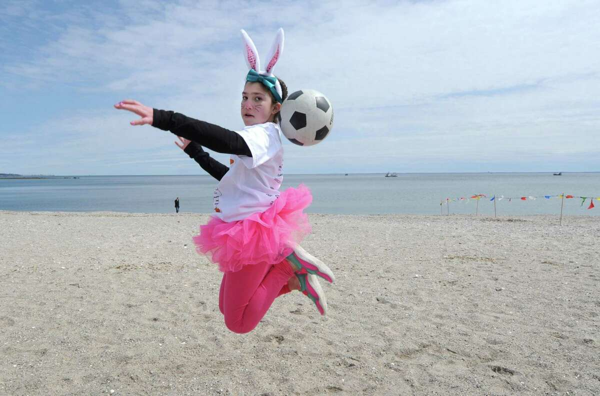 Olivia Fitch, 10, warms up with a soccer ball before the Special Olympics?' 50th Anniversary and Penguin Plunge, Saturday, April 7, 2018, at Compo Beach in Westport , Conn.