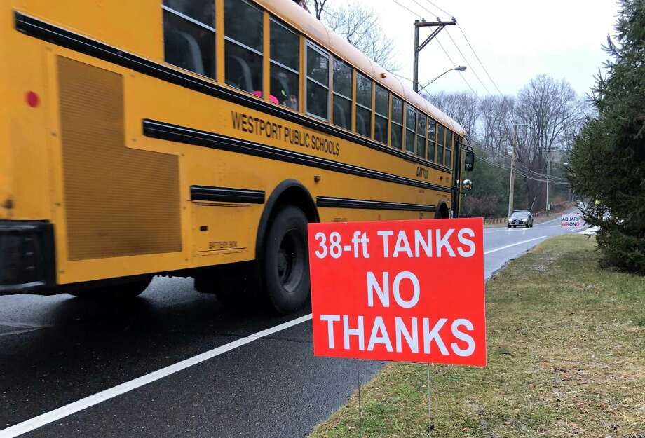 A school bus passes an anti-Aquarion tank sign in Westport. Photo: Contributed Photo
