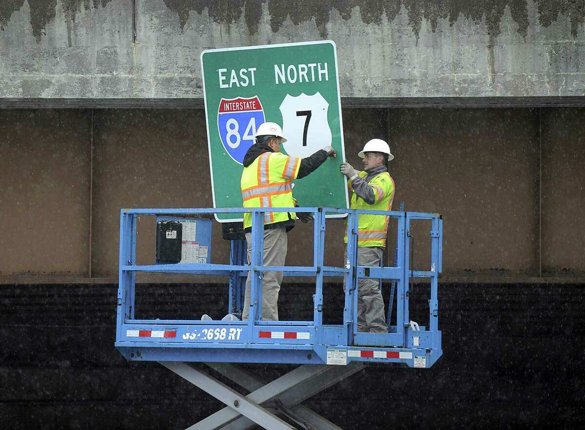 Workers put up signs Tuesday, April 3, 2018, under the I-84 overpass near Exit 6 in Danbury. Construction crews began work reconfiguring the exit and making upgrades to the roads in April 2015. The majority of the project, which encompasses parts of North Street and Padanaram Road - both parts of Route 37 - as well as the ramps off and on Interstate 84, was mostly completed in the fall with some punch list items wrapping up in the next few weeks.