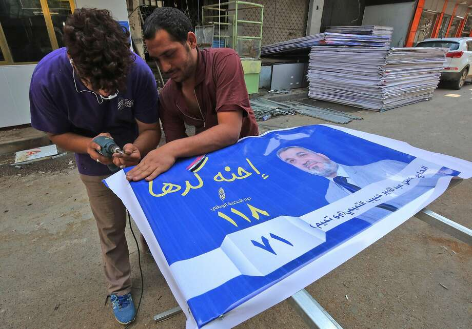 Iraqis prepare campaign posters for candidates in the upcoming parliamentary elections in Baghdad. Nearly 7,000 candidates will vie for 329 seats. Photo: Ahmad Al-rubaye / AFP / Getty Images