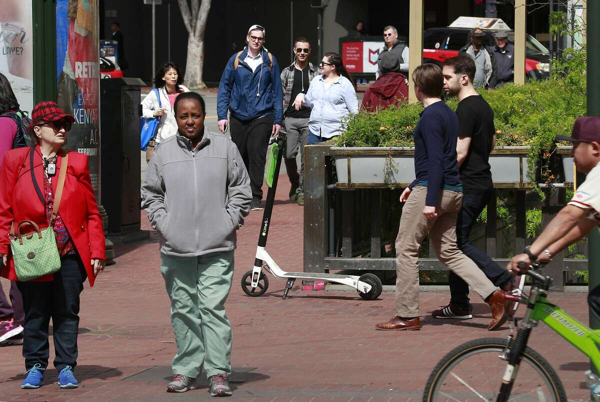 A Lime scooter parked along Market St. as pedestrians pass, seen on Mon. April 9, 2018, in San Francisco, Calif.