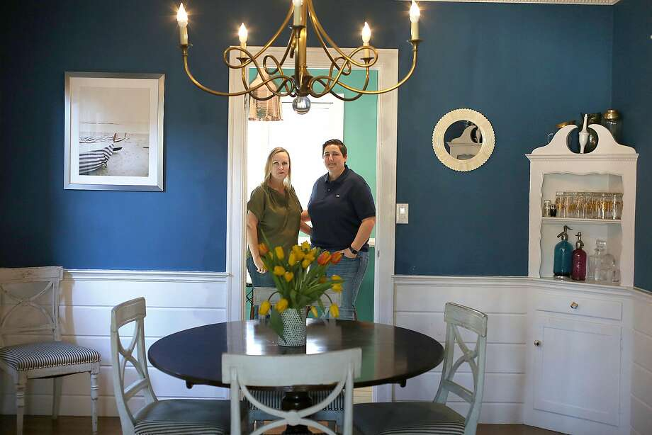 Interior designer Melanie Coddington (left) and partner Maggie Mesa at the threshold of their dining room painted bright blue. Photo: Liz Hafalia / The Chronicle