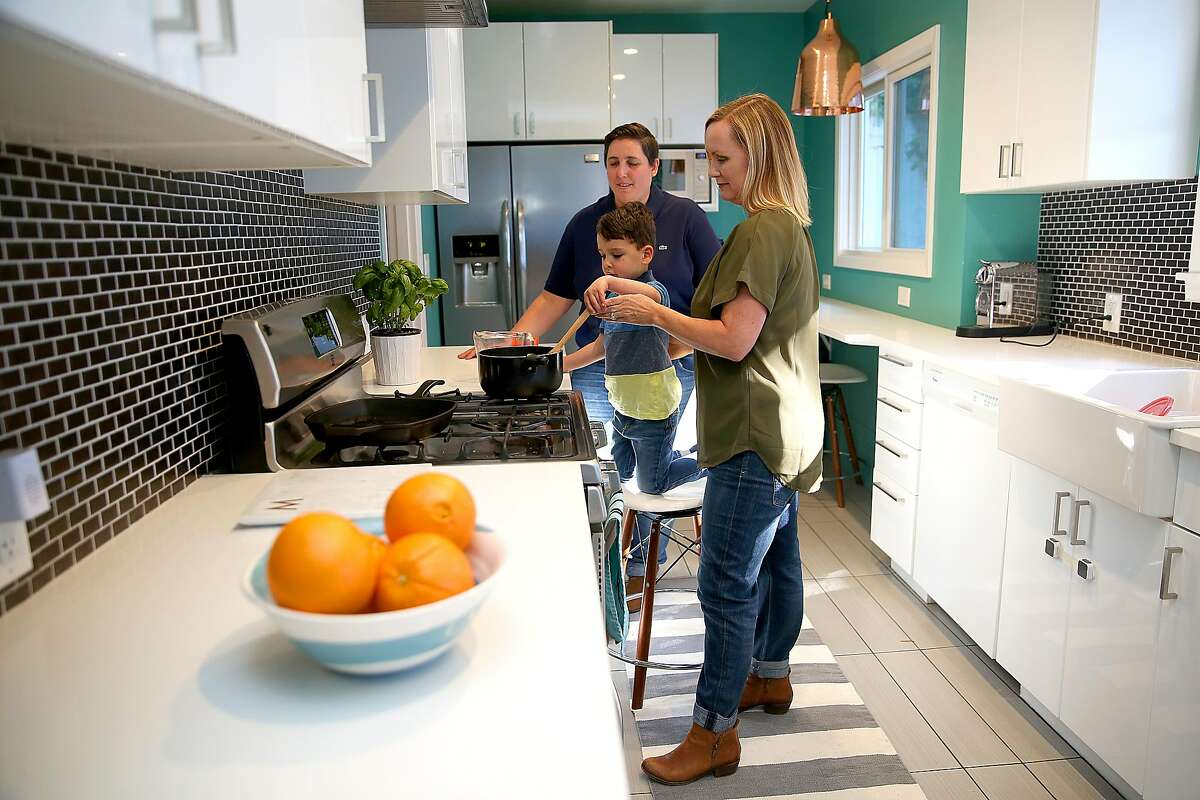 Interior designer Melanie Coddington (right) with her wife Maggie Mesa (left) and son Theo Mesa (middle), 4 years old, make pasta in the kitchen at home on Thursday, February 22, 2018, in Oakland, Calif.