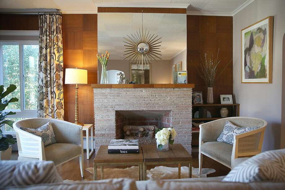 The original fireplace with walnut paneling and mirror with starburst mirror in the living room. Photo: Liz Hafalia / The Chronicle