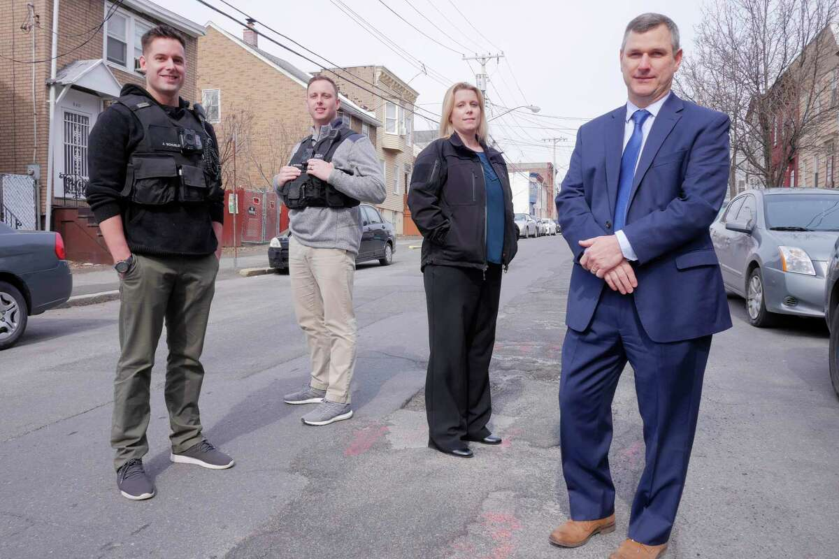 Albany Police Officers working with the LEAD Program, John Schueler, left, Benjamin Peterson, second from left, Albany Police Lieutenant of training and policy and overseeing the Albany LEAD Program, Melissa Gipson, and Brendan Cox, director of policing strategies for LEAD National Support Bureau, pose for a photo on Sheridan Ave. on Thursday, April 12, 2018, in Albany, N.Y. (Paul Buckowski/Times Union)