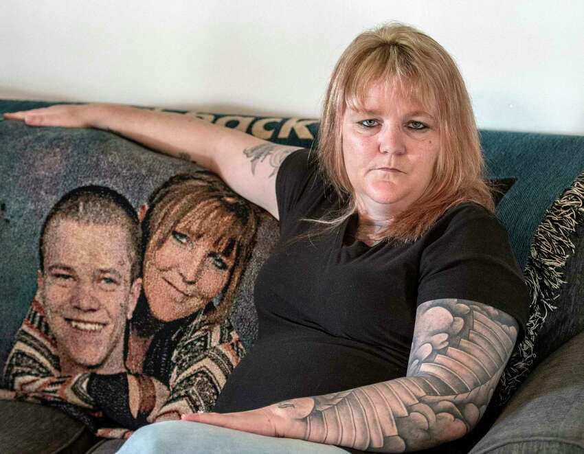 Tracy Minor sits on her couch at her home with a likeness of her son McKinley David Desnoyers on a blanket to her left Friday April 13, 2018 in Stillwater, N.Y. Her son died on Nov. 10, 2015 after an heroin overdose. (Skip Dickstein/Times Union)