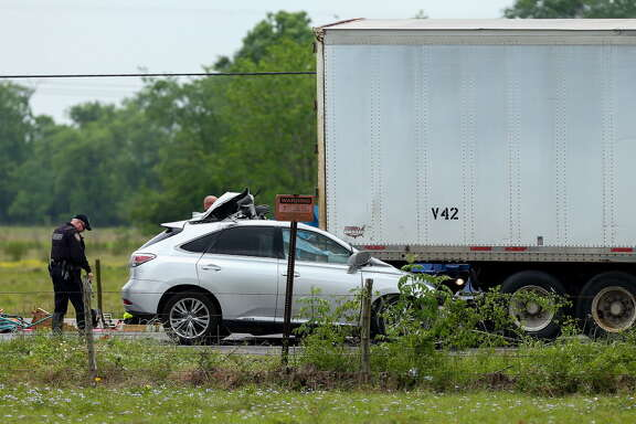 Harris County Sheriff's Office deputies investigate the scene of a fatal vehicle crash on FM 2920 near Lutheran Church Road Friday, April 13, 2018, in Tomball, Texas. A motorist in an SUV died after crashing into the back of an 18-wheeler.
