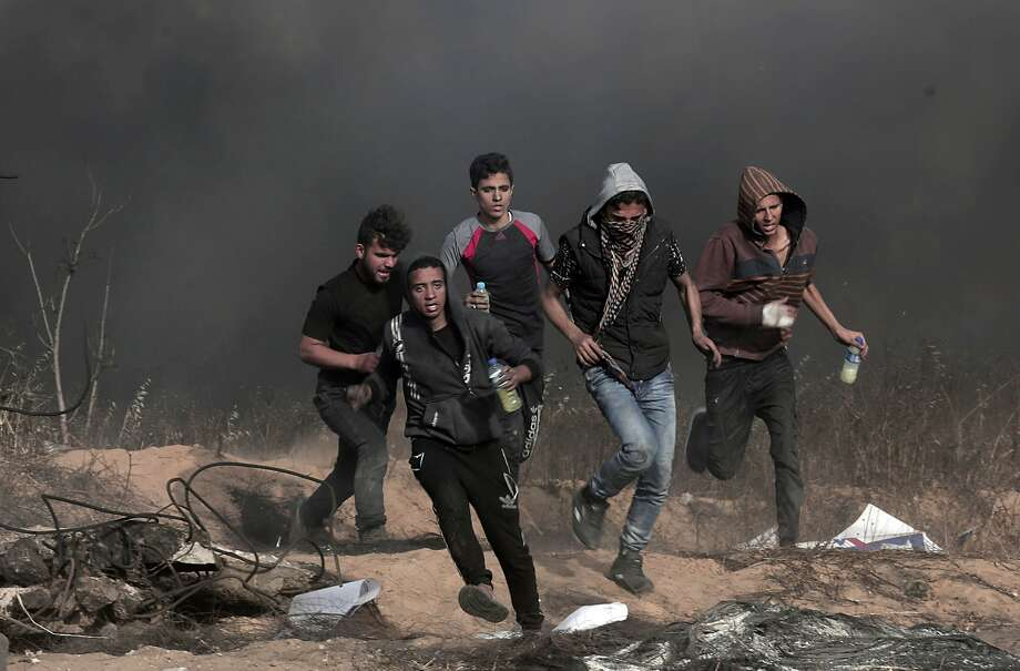 Palestinian protesters run after they burn tires during clashes with Israeli troops along Gaza's border with Israel. The demonstrations are part of a pressure campaign to break a decade-old blockade. Photo: Adel Hana / Associated Press
