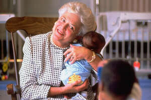 First Lady Barbara Bush holding baby while two-year-old child takes photo with a toy camera at a hospice for children with AIDS.