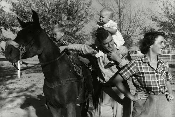George H. W. Bush with his wife, Barbara, and their children Pauline and George W. on horse in the yard of their Midland, Texas ranch.