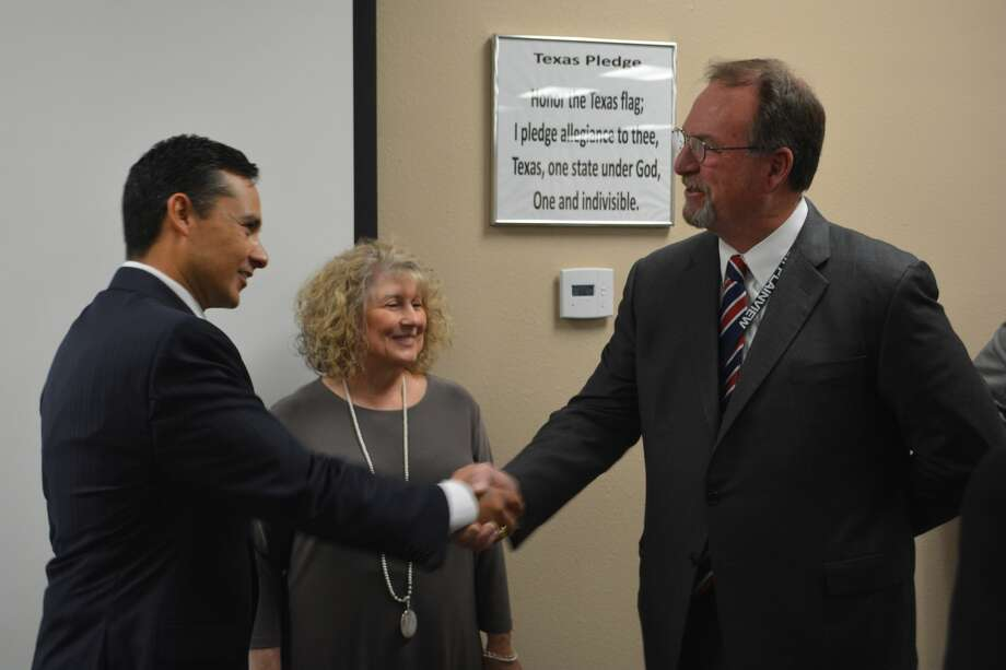 Dr. H.T. Sanchez (left), lone finalist to become Plainview ISD's next superintendent, shakes hands with Plainview High School Principal Brandt Reagan and PISD Trustee Cheryl Dickerson looks on. The handshake and cordial exchange took place Wednesday morning after school board members voted unanimously for Sanchez. Under state law, the district must wait at least 21 days (May 2) before offering Sanchez a contract. Photo: Doug McDonough/Plainview Herald