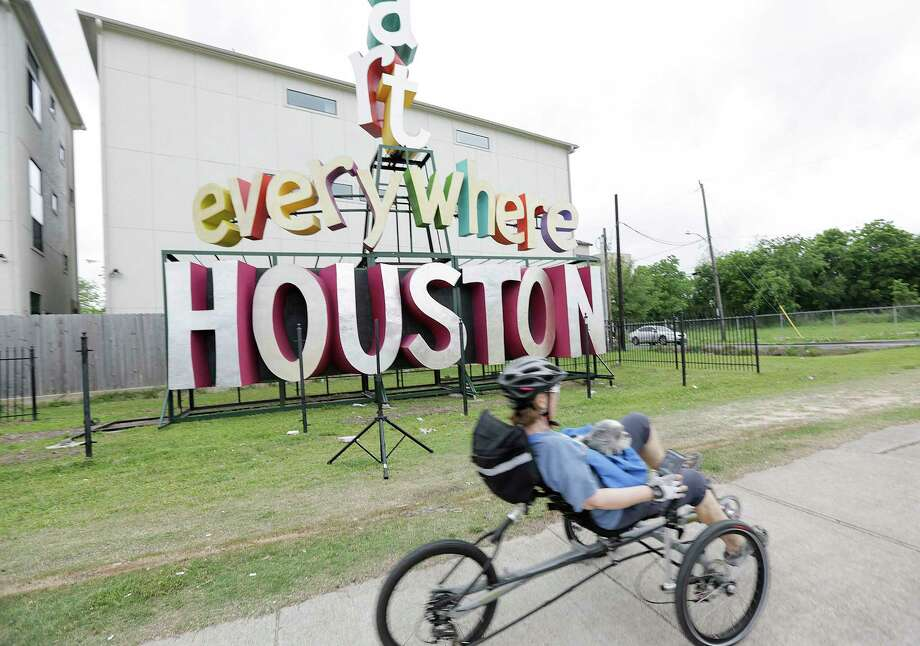 "Gail Wellenkamp rides with her dog, Gyan, past the latest sculpture by David Adickes off of I-10 near the Yale Street exit on  Friday, April 13, 2018, in Houston. The piece reading ""Art Everywhere Houston"" was erected Thursday and replaces Adickes ""We (heart) Houston,"" which is now located near the 8th Wonder Brewery. ""I really liked his last piece, and I like this one too,"" said Wellenkamp.See more photos of the piece installed this week ... Photo: Elizabeth Conley, Houston Chronicle / © 2018 Houston Chronicle"