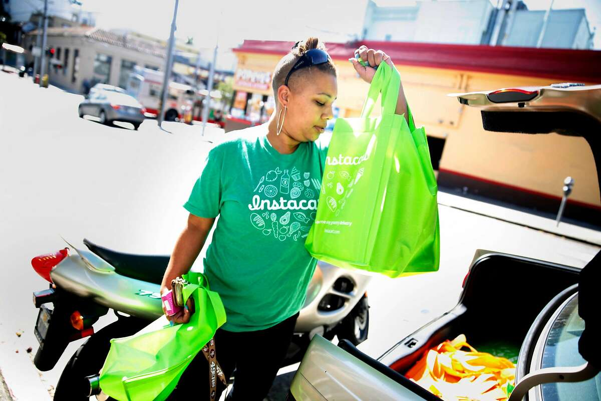 Instacart personal shopper, Tammara Dozier, places a customer's order into her car for delivery on Thursday, July 24, 2014 in San Francisco, Calif. Instacart classifies shoppers for the service as independent contractors.