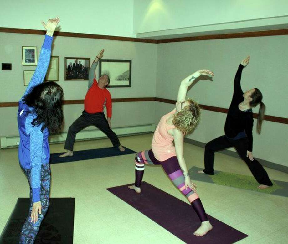 From left, Debbie McLean, David Jaroch, Lindsey Kramer and Amanda Sulkowksi practice the warrior pose this week during a yoga class at Ubly's Sleeper Public Library. (Brenda Battel/Huron Daily Tribune)