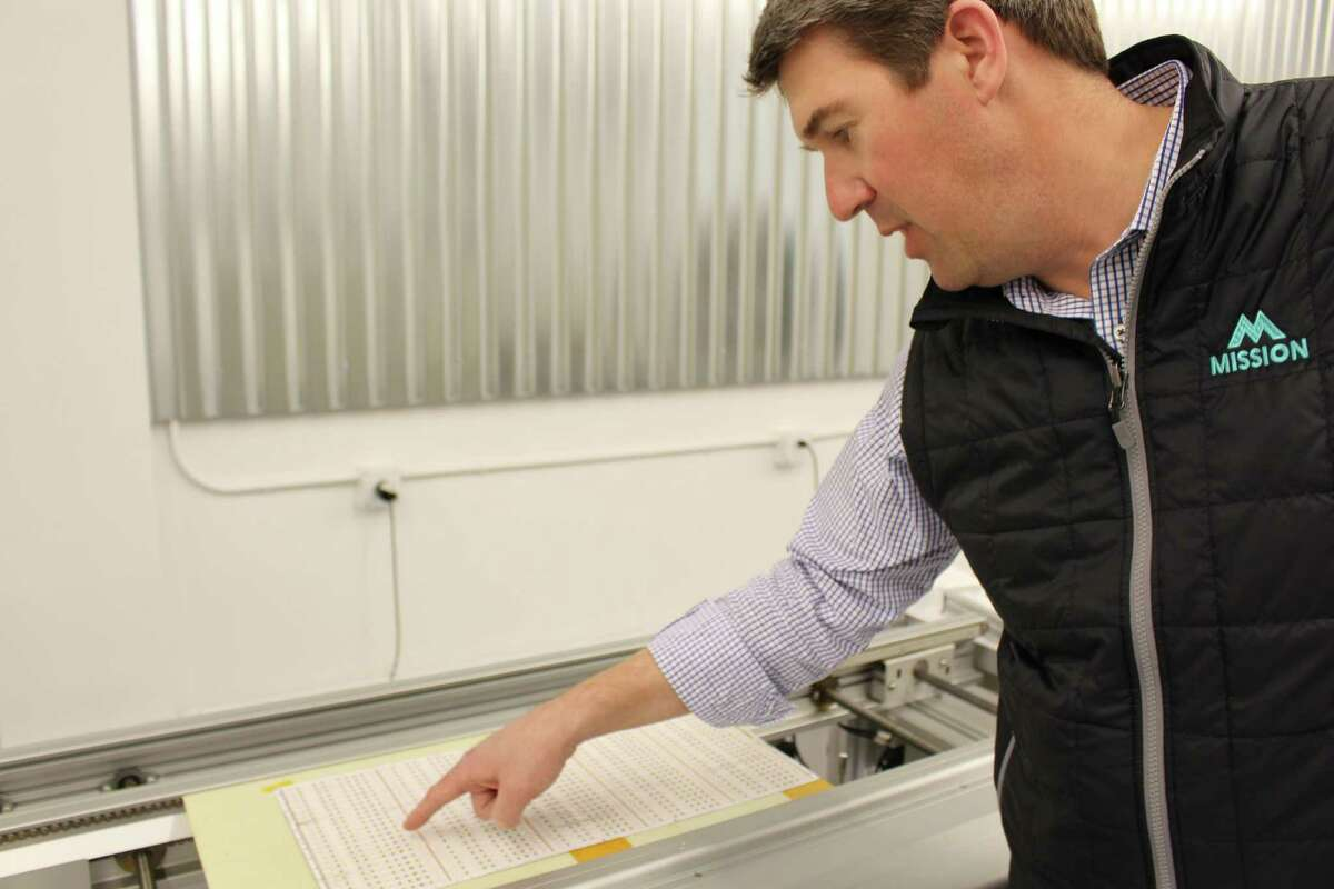 Gean Tremaine, president of Q-Tran, Inc. inspects newly mounted LED lights in the Milford-based company's new expansion.