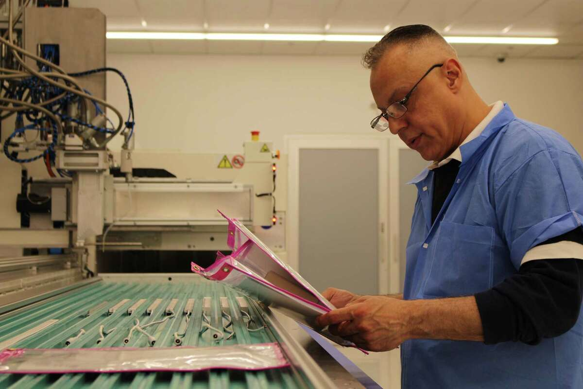 Employee Felix Cortez working with Q-Tran's Q-Cap encapsulation system.