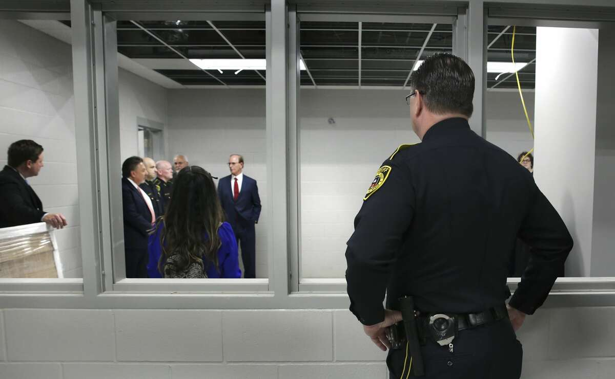 A Bexar County Sheriff official, right, looks through an intake interview window at other Bexar County officials including Bexar County Sheriff Javier Salazar and County Judge Nelson Wolff, during a tour of the new Bexar County Justice Intake and Assessment Center which has been built next to the Bexar County Jail, on Friday, April 13, 2018.