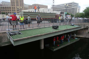 Workers and volunteers lower a barge into the San Antonio River Friday April 13, 2018 on Nueva street. The barges will be used for the upcoming annual Texas Cavaliers Fiesta River Parade. A total of 31 barges were loaded into the river by about 50 members of the Texas Cavaliers. The parade takes place April 23, 2018. The Texas Cavaliers, founded in 1926, is a volunteer organization dedicated to raising money and supporting San Antonio childrens' charities through its foundation.