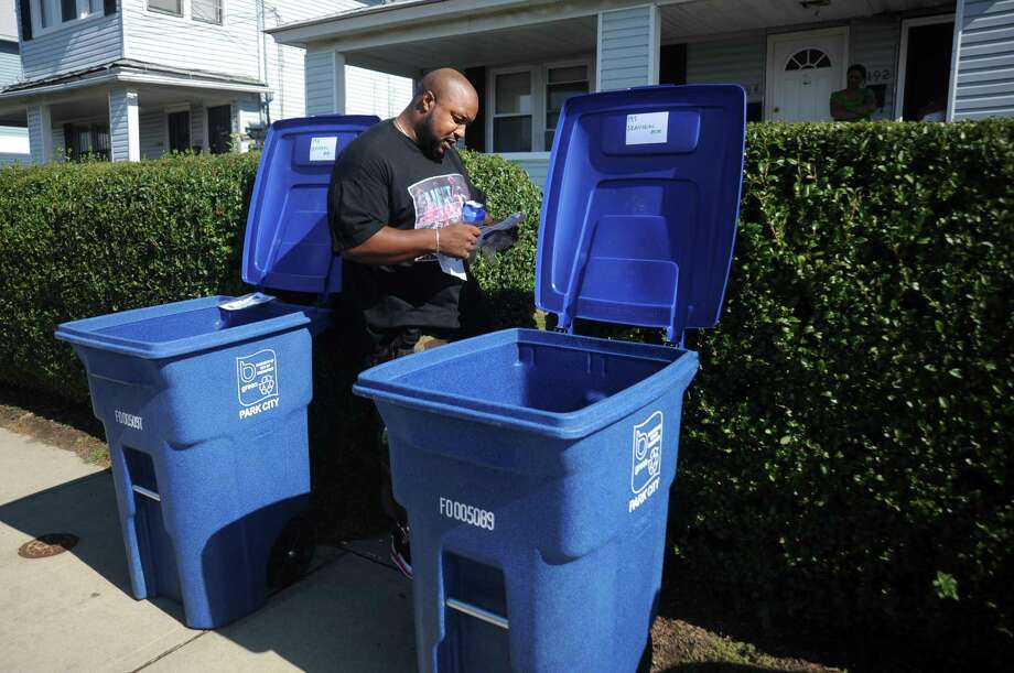 Rayshawn Smith reads the pamphlet he received with a new blue Toter bin. In Torrington, Mayor Elinor Carbone is seeking ways to encourage residents to properly dispose of their waste, allowing the city to earn points and funding. The city uses Toters for recycling and regular trash bins for garbage. Photo: Autumn Driscoll / ST / Connecticut Post