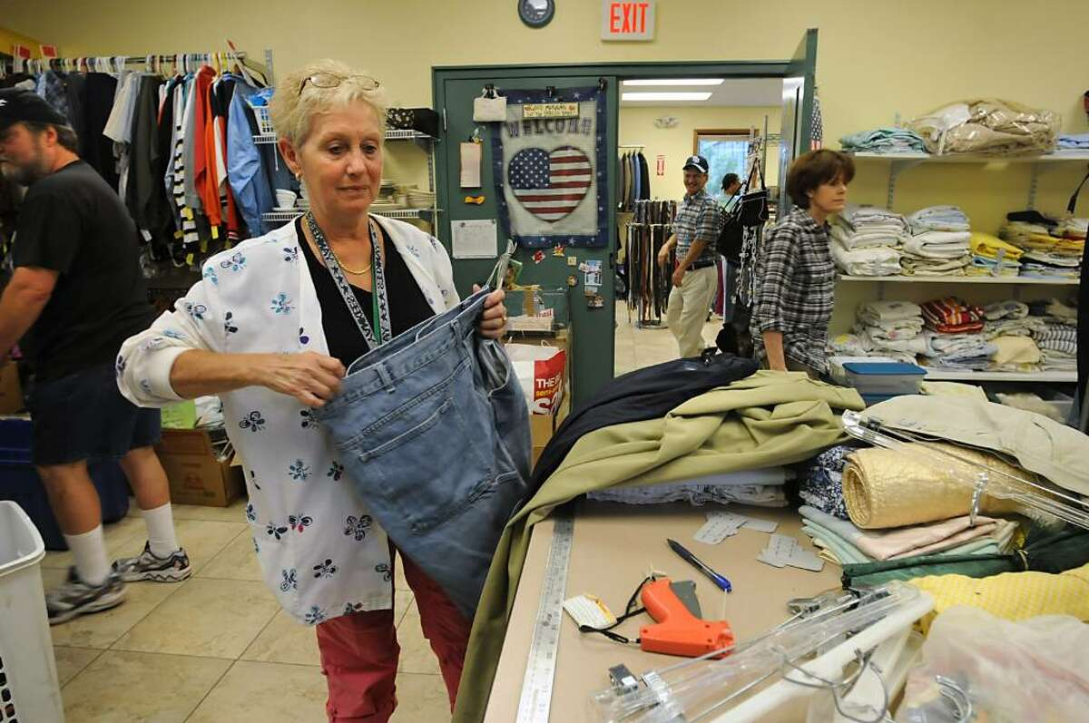 Volunteer Donna Drum, of Rexford, checks the size of a pair of jeans to mark it with tag in the Blessingdales section of the Capital City Rescue Mission in Albany, NY on June 16, 2010. (Lori Van Buren / Times Union)