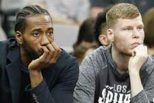 San Antonio Spurs forward Kawhi Leonard and center Davis Bertans watch first half action against the Memphis Grizzlies from the bench Monday March 5, 2018 at the AT&T Center.