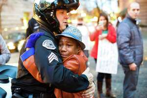 FILE - In this Nov. 25, 2014, file photo provided by Johnny Nguyen, Portland police Sgt. Bret Barnum, left, and Devonte Hart, 12, hug at a rally in Portland, Ore., where people had gathered in support of the protests in Ferguson, Mo. The SUV carrying the Hart family, from Woodland, Wash., that plunged off a coastal cliff near Mendocino, Calif., recently, killing all passengers, accelerated straight off the cliff and authorities said the deadly wreck may have been intentional. (Johnny Huu Nguyen via AP, File)