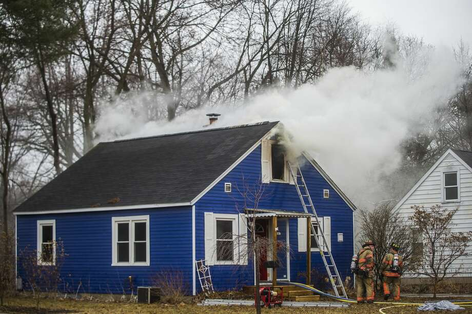 Midland firefighters work to put out a house fire at 1414 Ohio Street on Friday, April 13, 2018 in Midland. (Katy Kildee/kkildee@mdn.net) Photo: (Katy Kildee/kkildee@mdn.net)