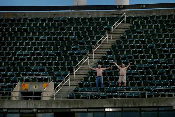 Oakland Athletics fans take their shirts off as they're broadcasted in the coliseum before an MLB game between the Athletics and Los Angeles Angels at the Oakland Coliseum, Friday, March 30, 2018, in Oakland, Calif.
