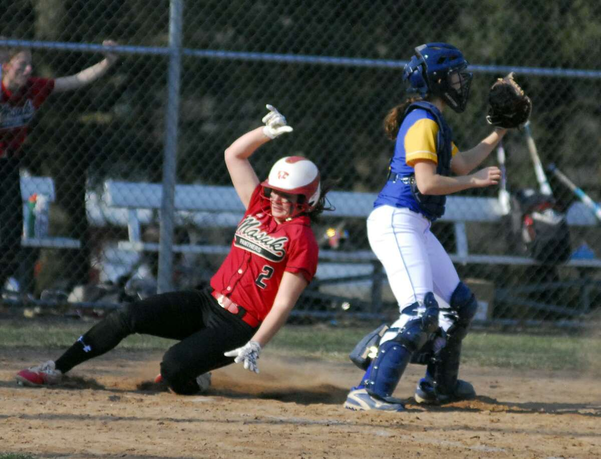 Masuk's Alexa Bacoulis slides into home plate during a game against Newtown on Friday.