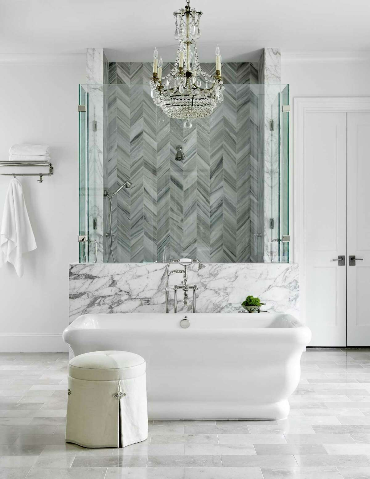 After: In a gray-white palette, the dazzling master bathroom now could grace the cover of any home decor magazine. Carrara marble laid in a herringbone pattern adds personality to the shower. In front of the shower sits a freestanding bathtub in a sculptural design.