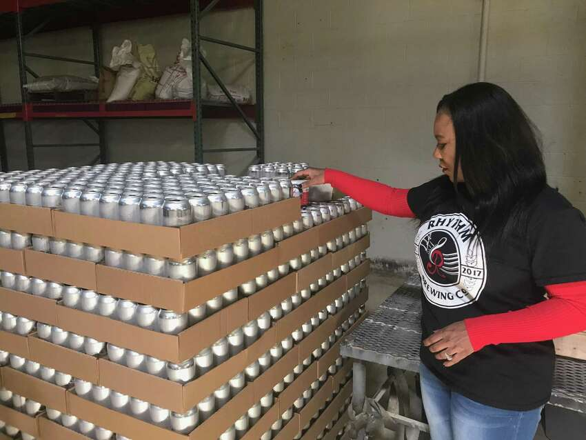 Pictured: Alisa Bowens-Mercado hold a six-pack of beer from her brewery, Rhythm Brewing Co.