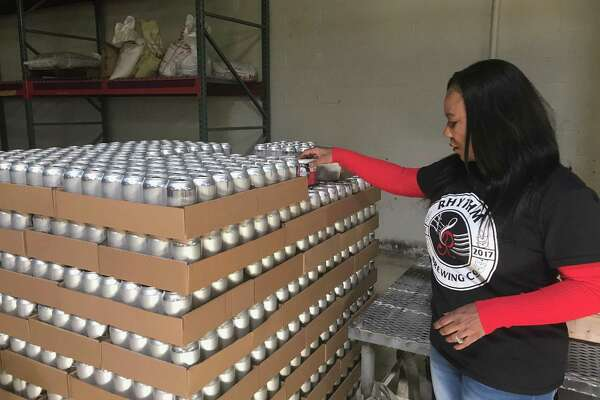 Alisa Bowens-Mercado hold a six-pack of beer from her brewery, Rhythm Brewing Co., on Friday.