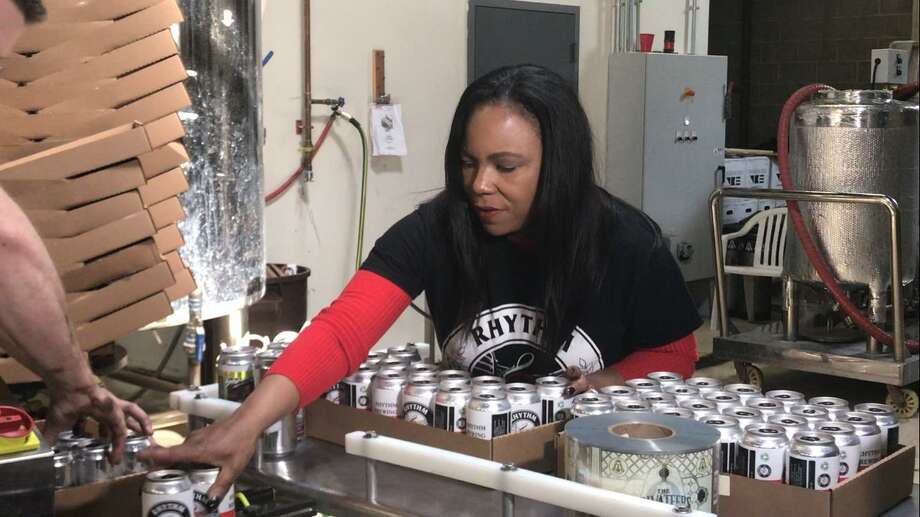 Alisa Bowens-Mercado hold a six-pack of beer from her brewery, Rhythm Brewing Co. Photo: Hearst Connecticut Media