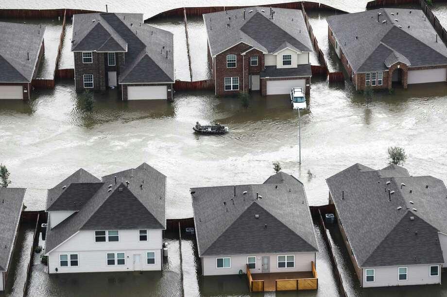 A boat runs past houses flooded by Tropical Storm Harvey on Tuesday, Aug. 29, 2017, in Spring. ( Brett Coomer / Houston Chronicle ) Photo: Brett Coomer, Staff / Houston Chronicle / Internal