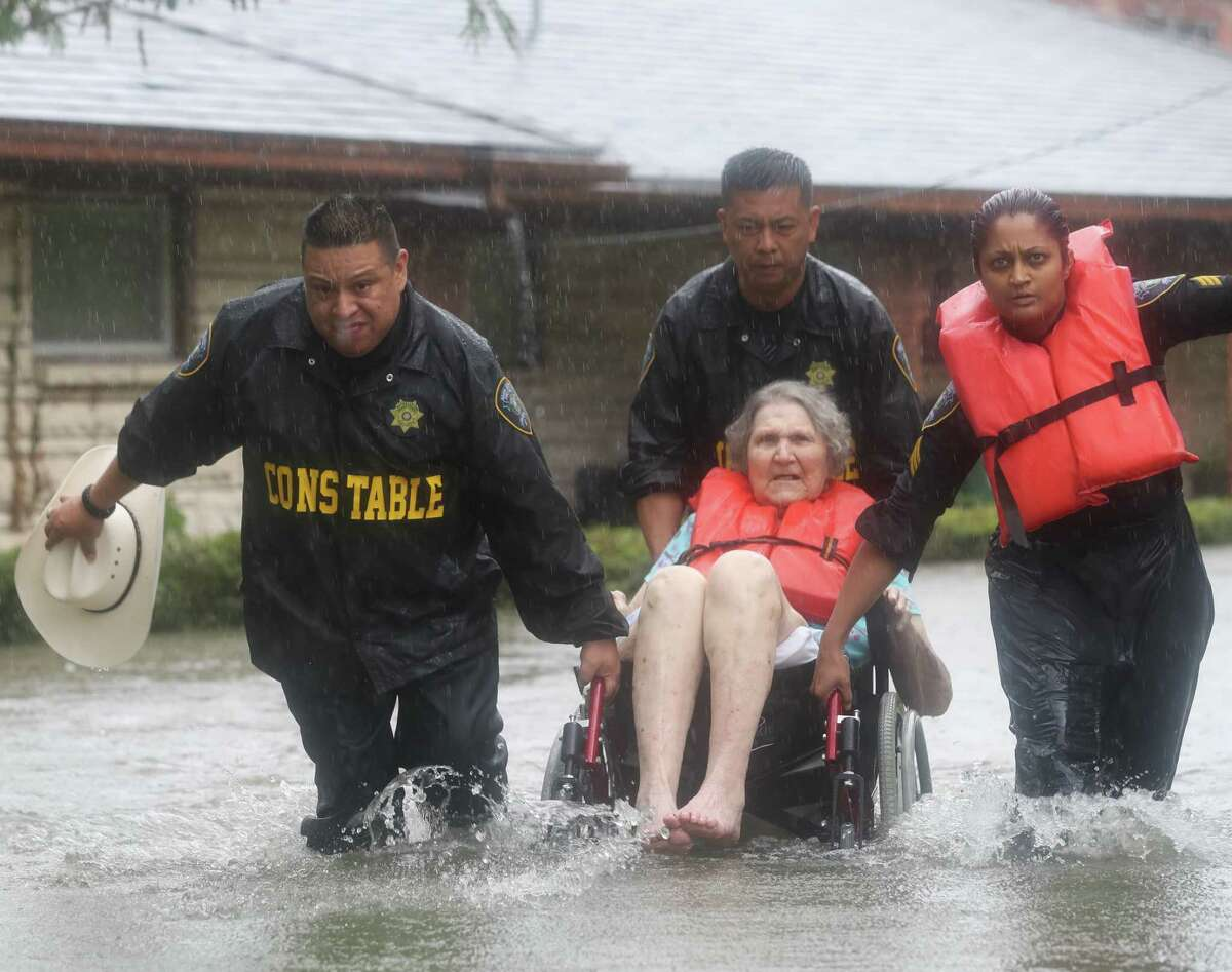 Precinct 6 Deputy Constables Sgt. Paul Fernandez, from left, Sgt. Michael Tran and Sgt. Radha Patel rescue an elderly woman from rising water on North MacGregor Way, near Brays Bayou, after heavy rains from the remnants of Hurricane Harvey on Aug. 27, 2017. ( Jon Shapley / Houston Chronicle )